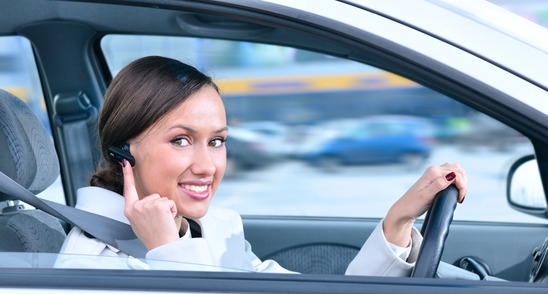 beautiful woman driver is safely talking phone in a car using a